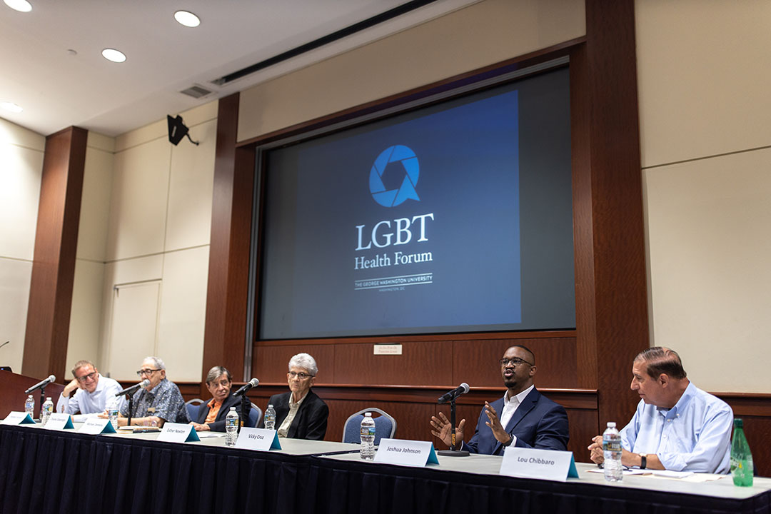 "A row of panelists speak at the head table in front of a sign reading ""LGBT Health Forum"""
